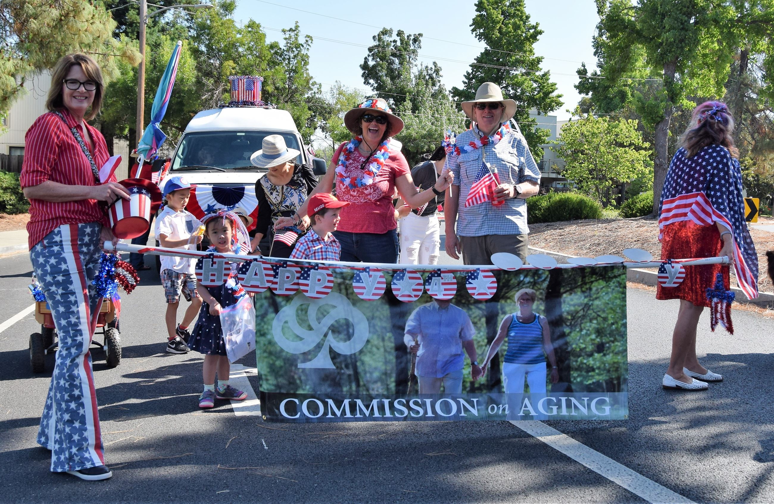 Parade participants holding the commission banner in front of the senior van